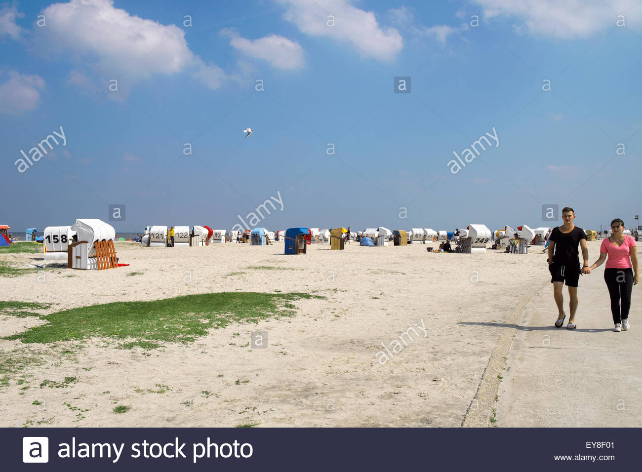 A couple walks by Strandkörbe, or beach chairs, in Schillig, Wangerland, Germany. - Stock Image