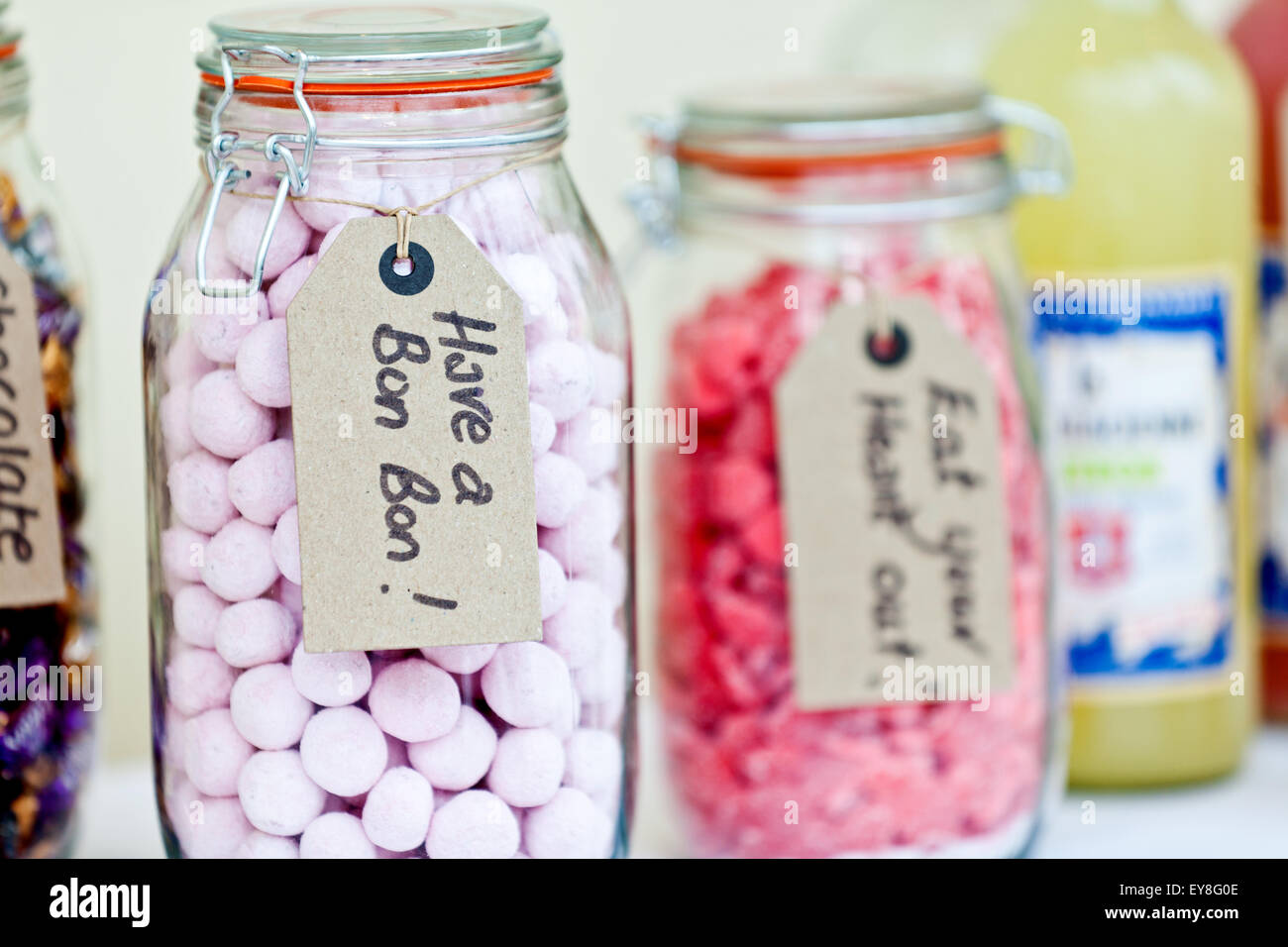 Assorted sweets arranged in jars on a table at a wedding reception. The trweats include Bon Bons and are all marked - Stock Image