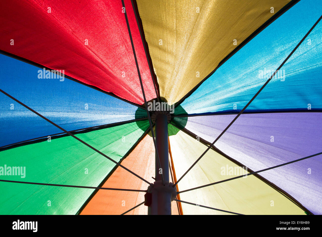 a colorful rainbow colored beach umbrella seen from below Stock Photo