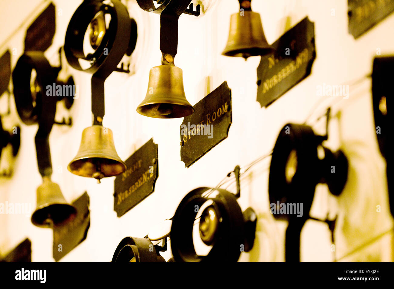 A row of servants bells suspended in the hallway of an English stately home. Historical used to summon serving staff - Stock Image