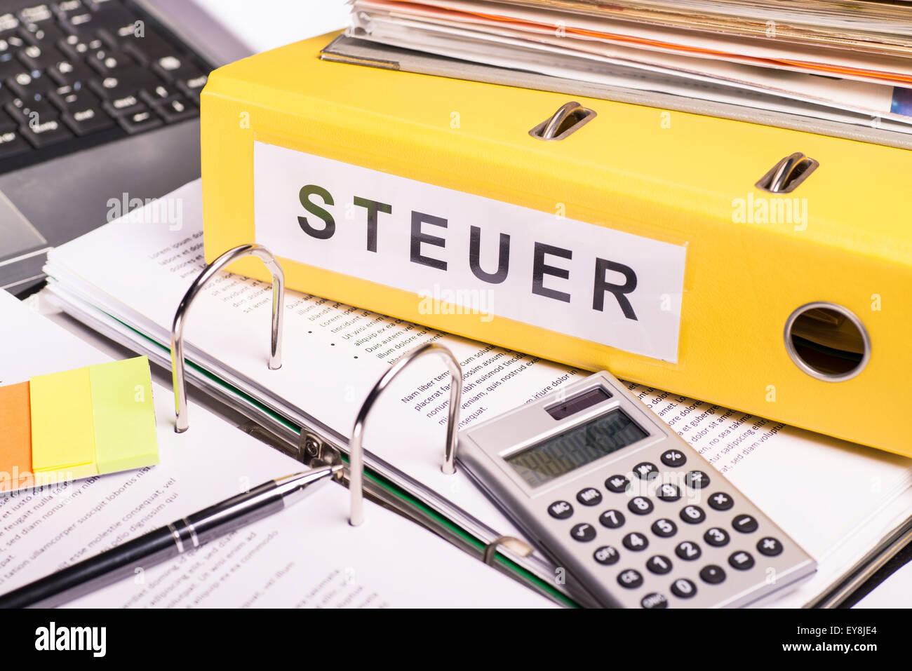Yellow file folder labeled tax - Stock Image