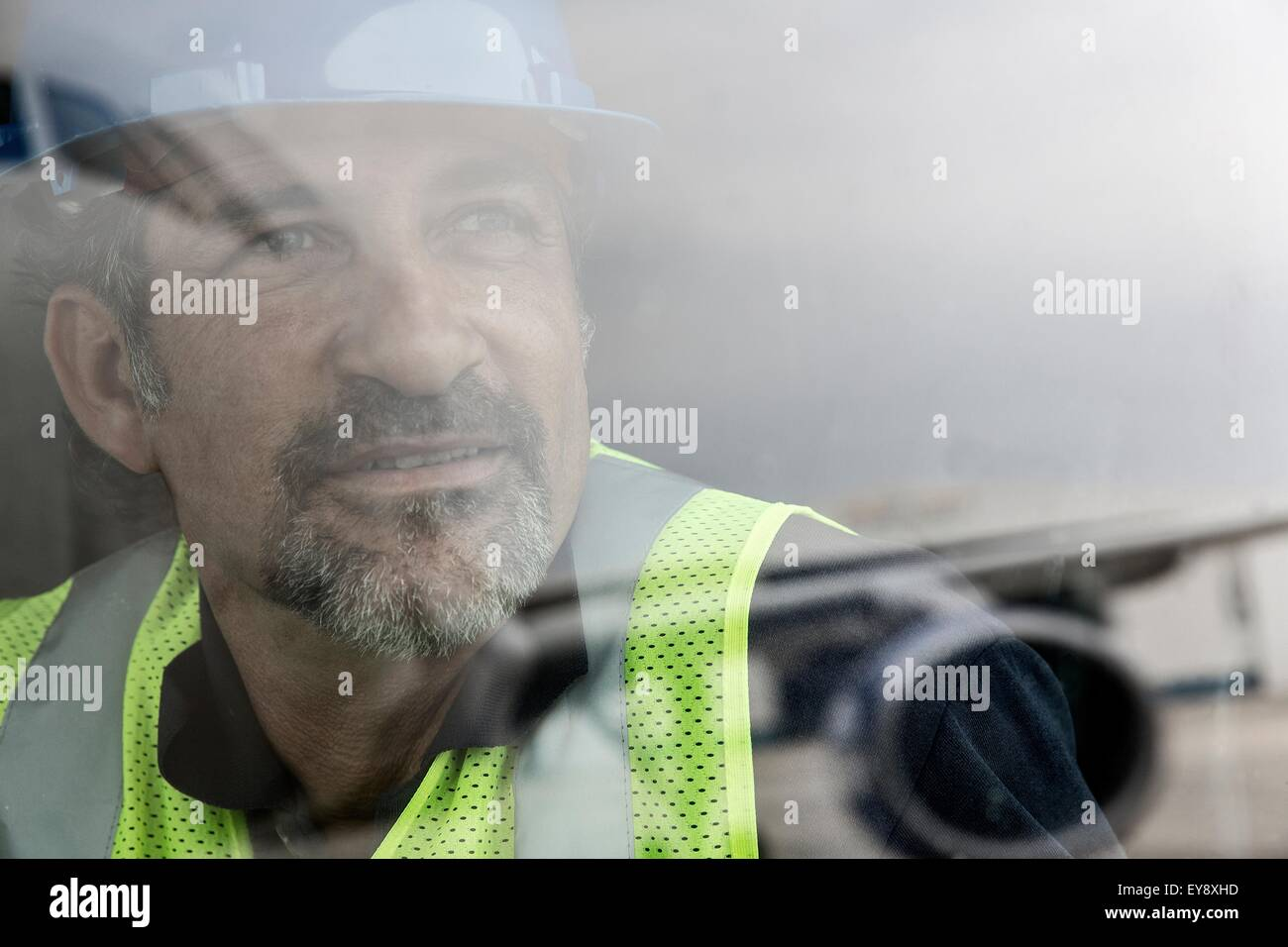 Portrait of airport worker looking out of window at airplane Stock Photo