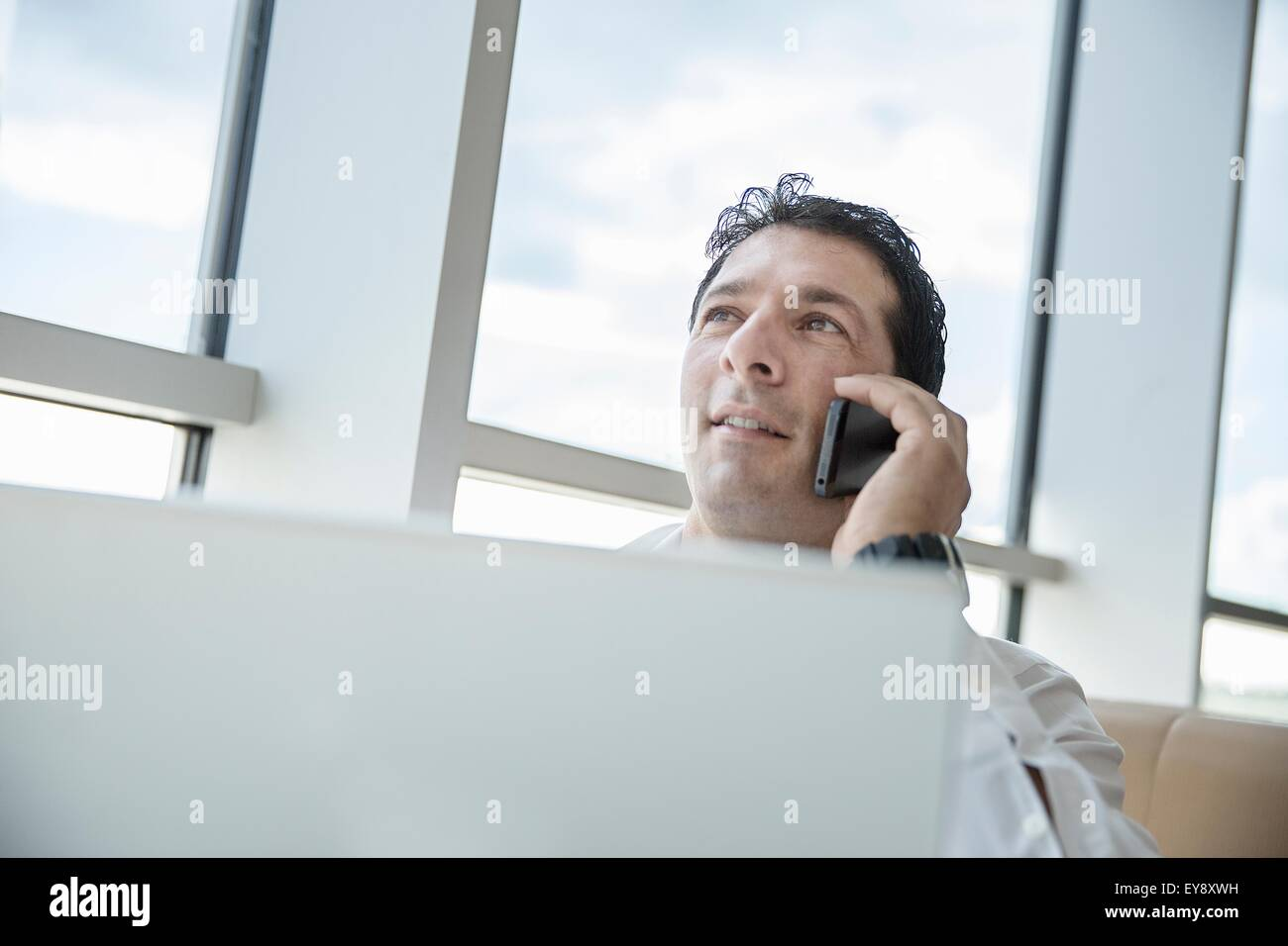 Man in airport lounge, talking on smartphone - Stock Image