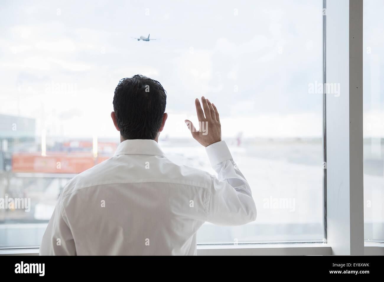 Man at airport window, waving - Stock Image