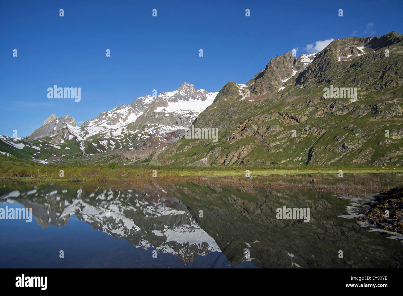 Reflection of mountains of the Mont Blanc massif and the Limestone Pyramids in  Lago Combal lake, Val Veny, Italian - Stock Image