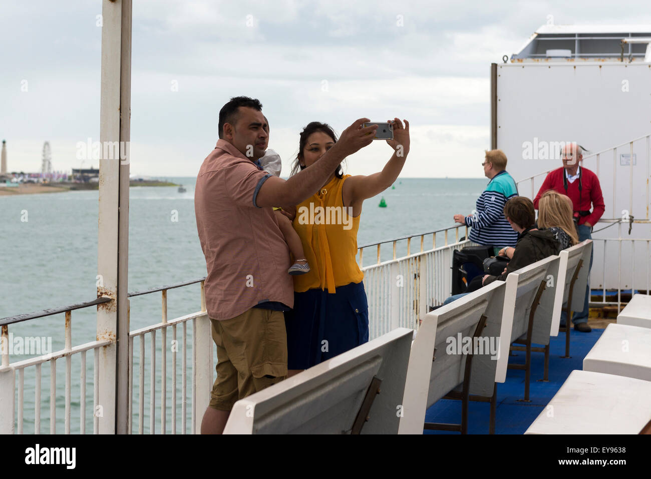 young to middle aged couple on ferry boat holding baby using a iphone to take a family selfie photograph - Stock Image