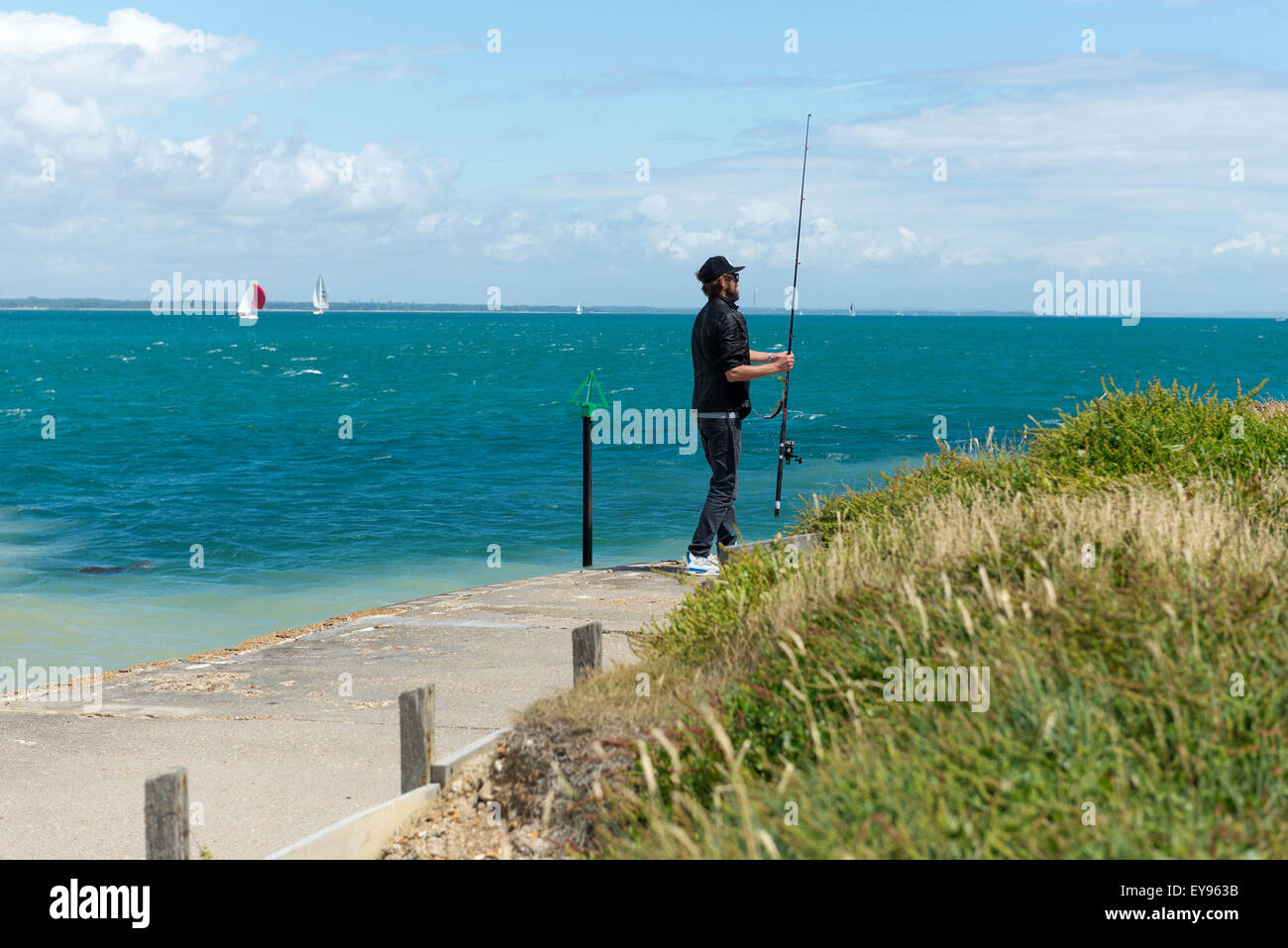 young male standing on foreshore fort victoria isle of wight holding a fishing rod standing with his back to the - Stock Image