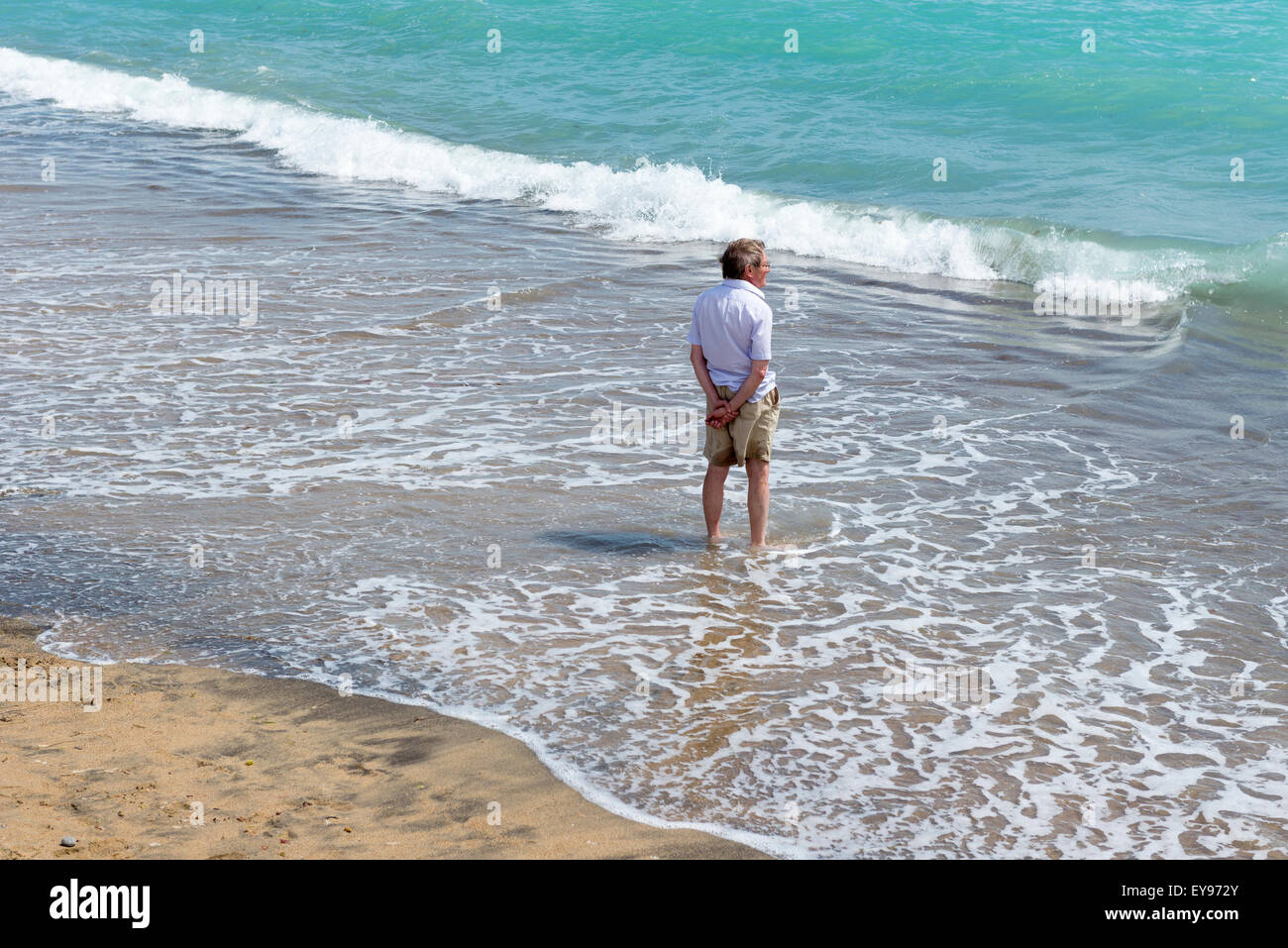 middle aged man wearing shorts and summer shirt standing ankle deep in the surf on a sandy beach at freshwater isle - Stock Image