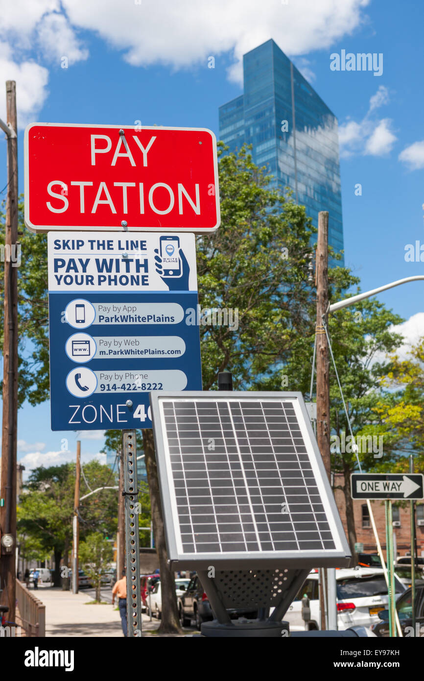 A solar powered multi-space pay station at a municipal parking lot in White Plains, New York. - Stock Image