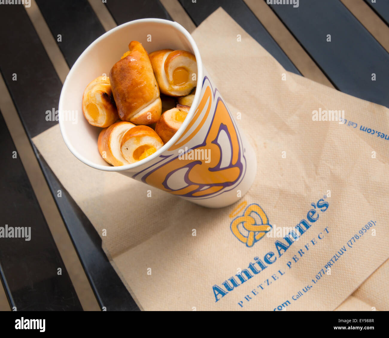 Image of a cup of cheese filled Auntie Anne's pretzel nuggets on brand napkins on mall food court bench. - Stock Image