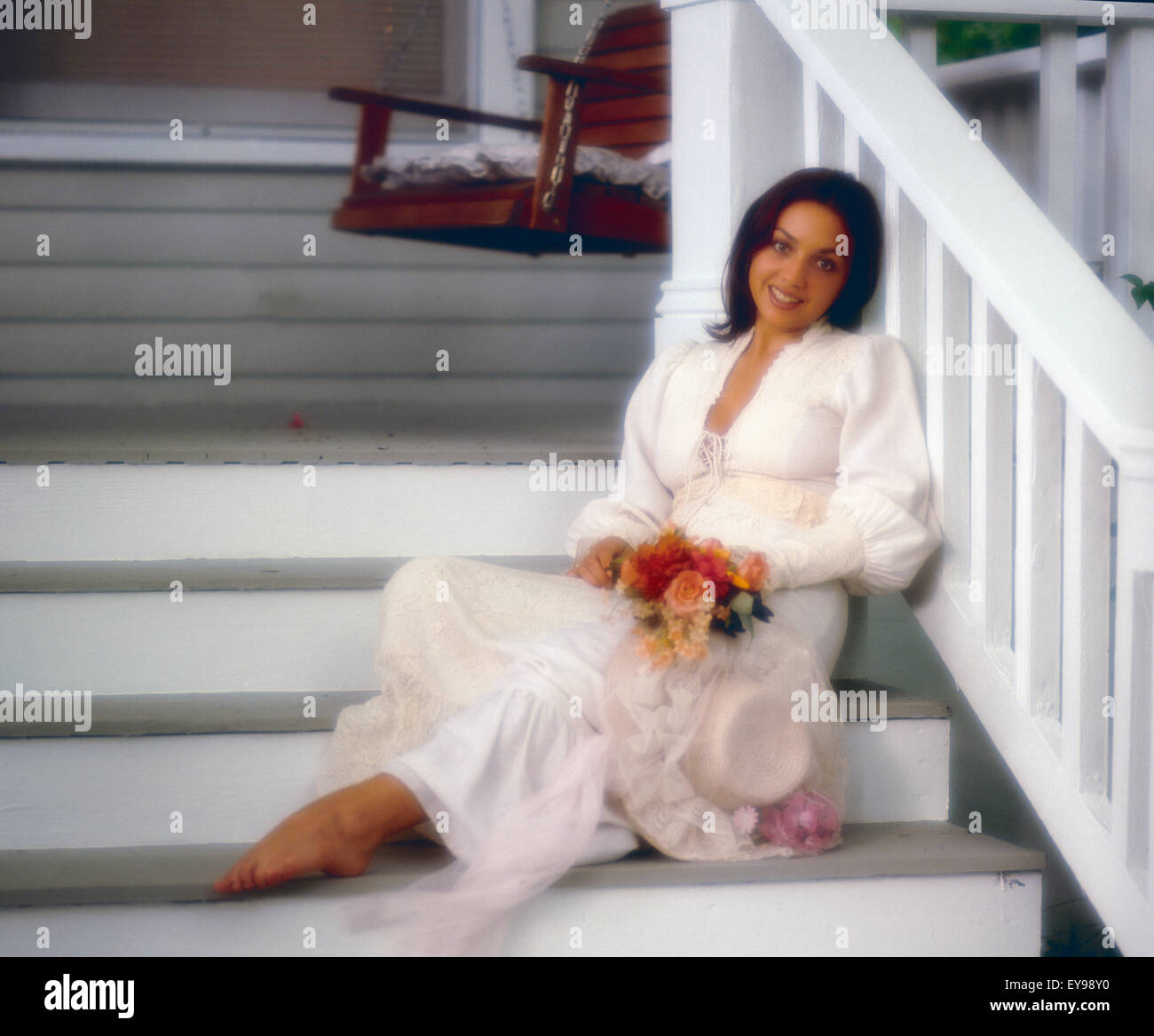 Pretty Woman Sitting On The Steps Of A Wooden House Wearing