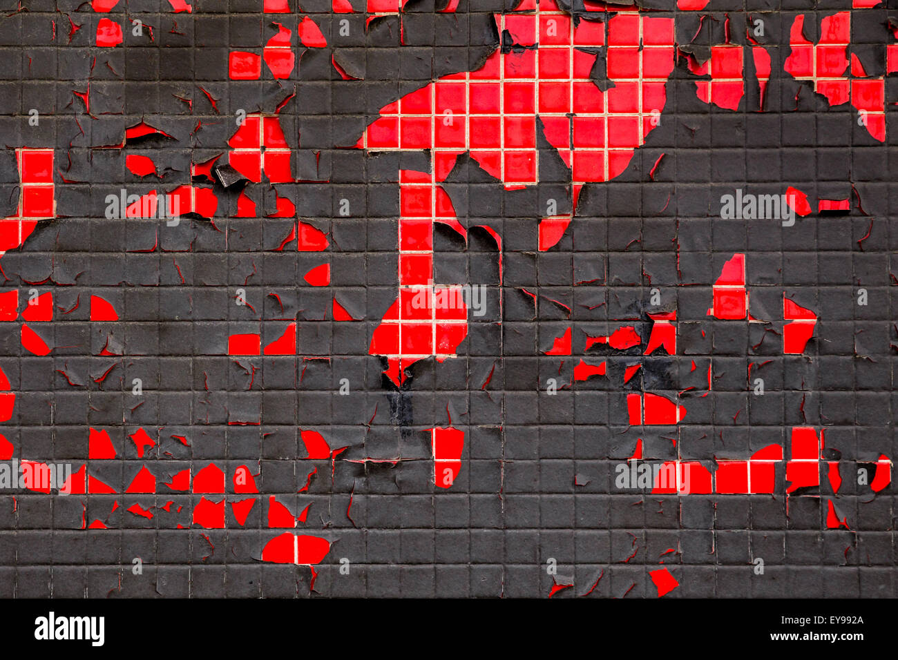 Grungy red and black tile and peeling paint wall - Stock Image