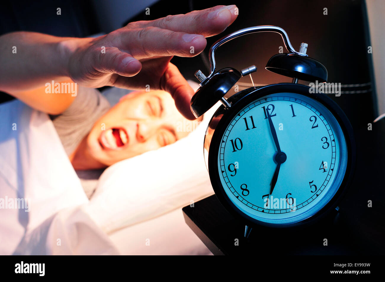 young caucasian man in bed yawns while stops the alarm clock at 7 in the morning - Stock Image