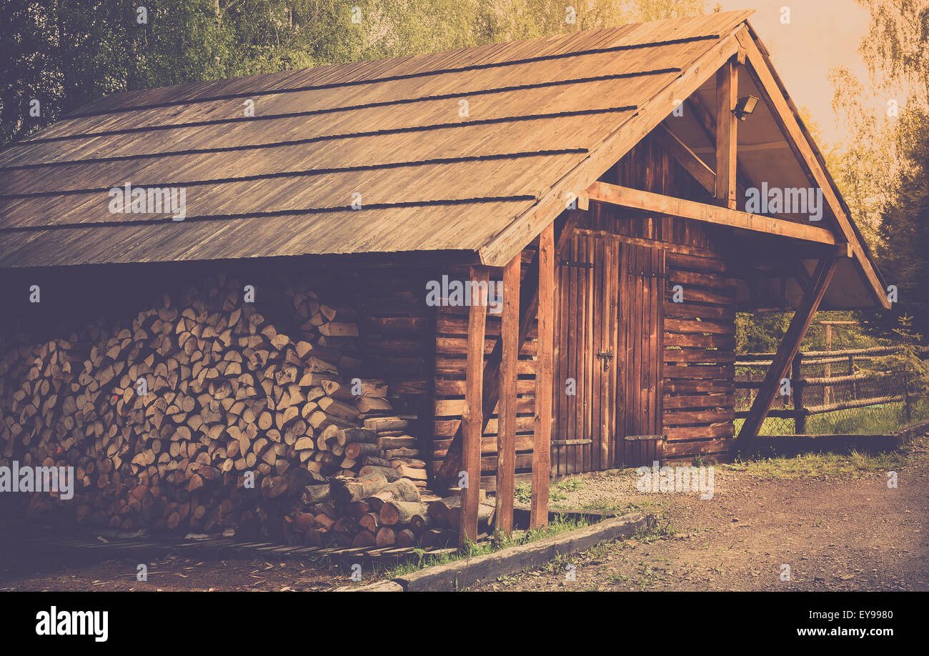 Wooden shed and prepared logs somewhere in forest Stock Photo