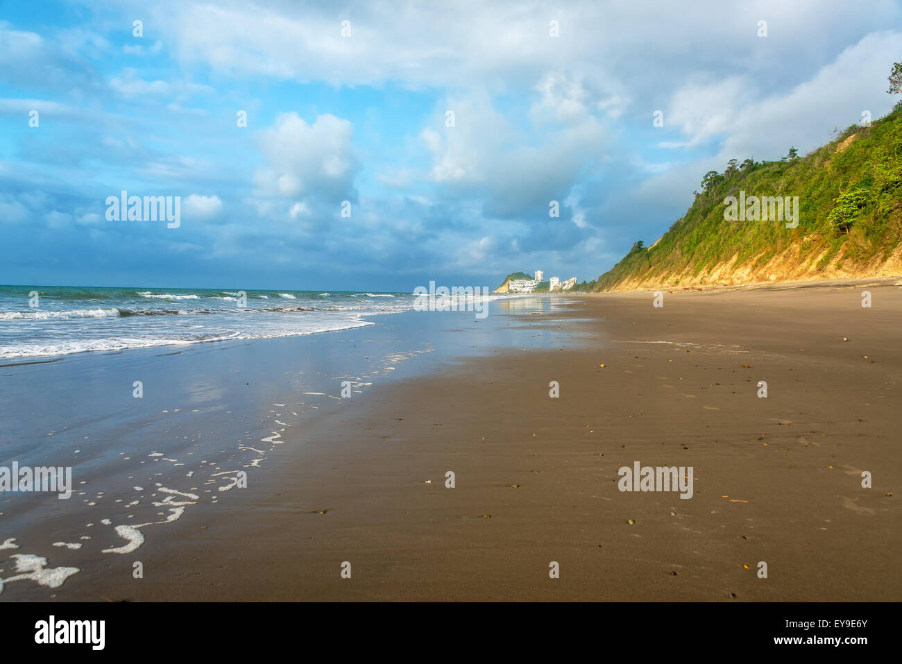 Long stretch of beach next to green hills in Same, Ecuador - Stock Image