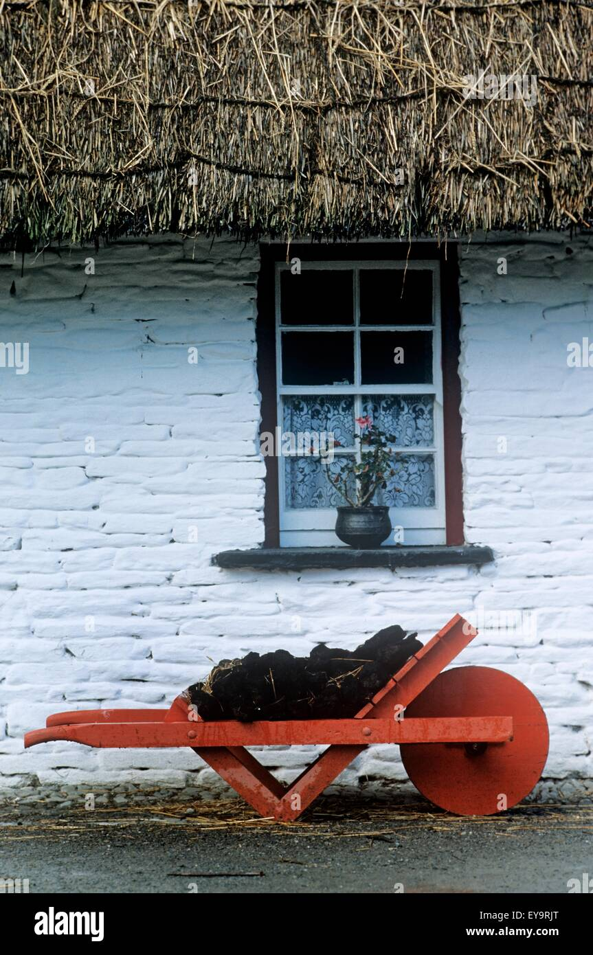 Wheelbarrow In Front Of A Window Of A Cottage, Bunratty Folk Park, Bunratty, County Clare, Republic Of Ireland - Stock Image