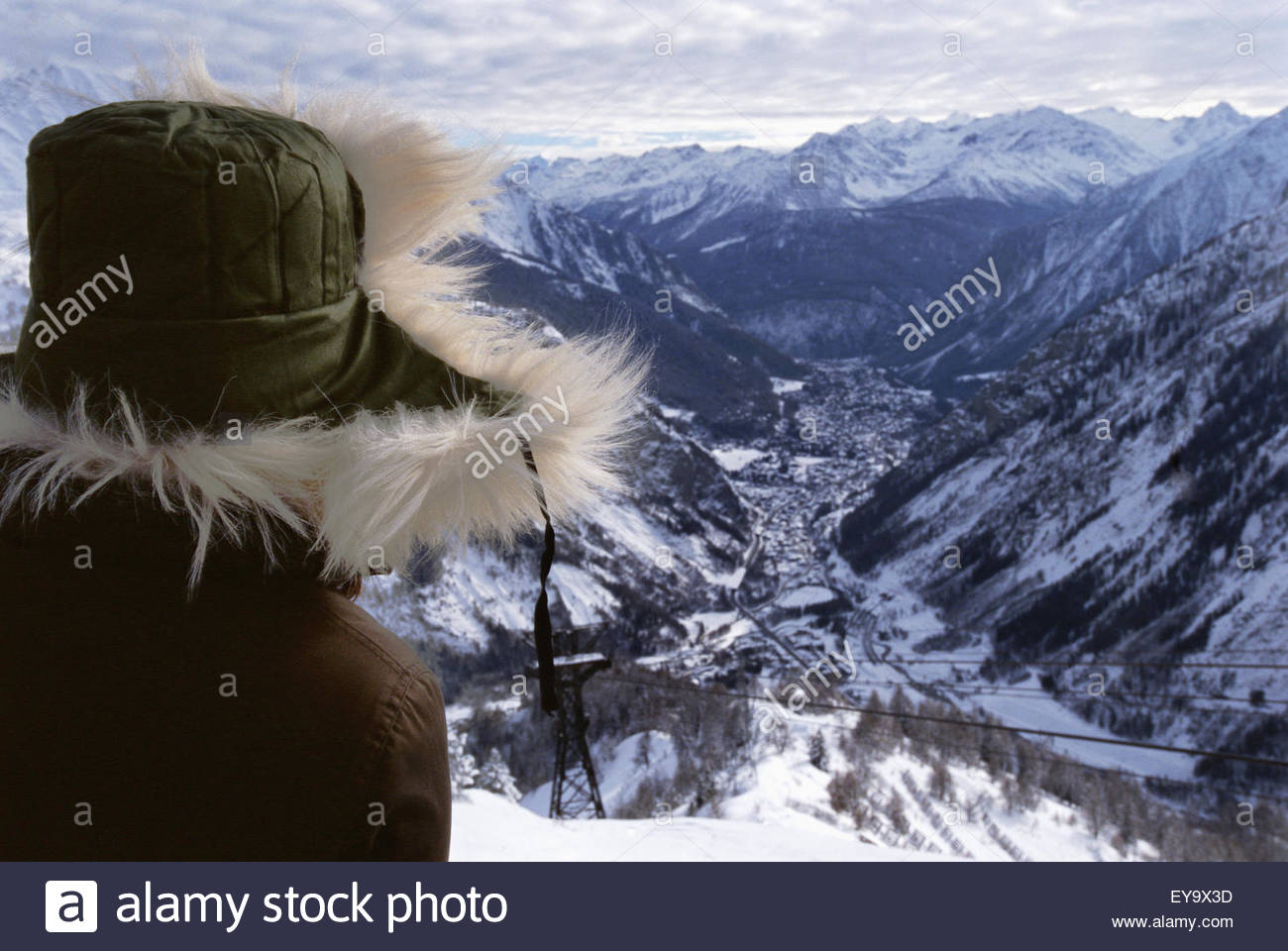 Woman In Fur Trimmed Hat And Snowcapped Mountains - Stock Image