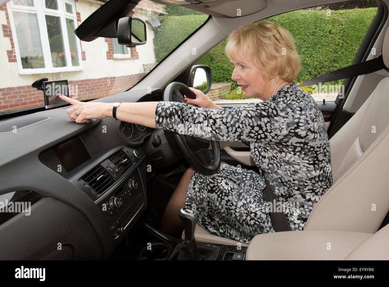 Elderly woman car driver adjusting satnav before commencing her journey - Stock Image