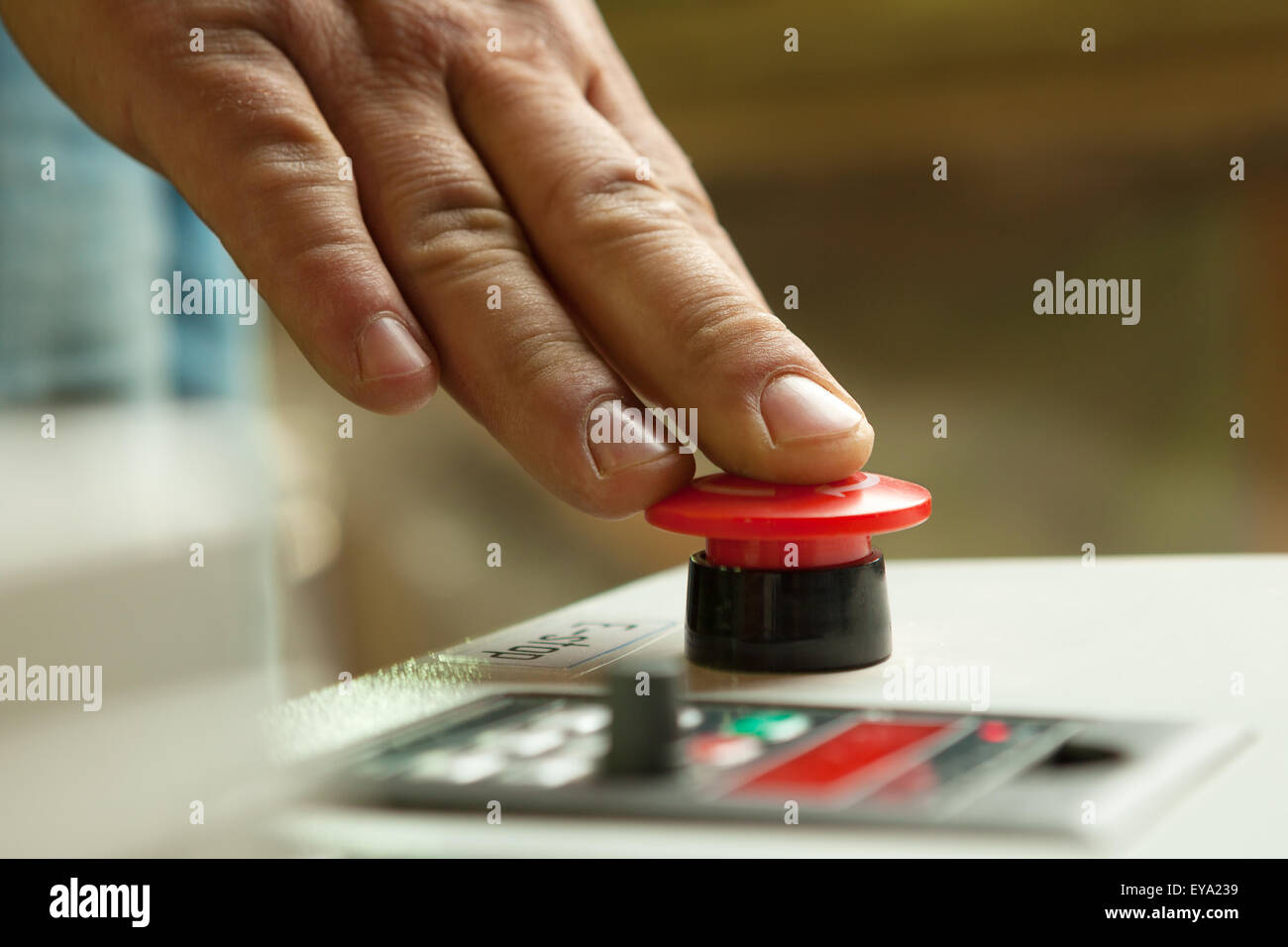 Male hand pushing emergency red stop button. - Stock Image