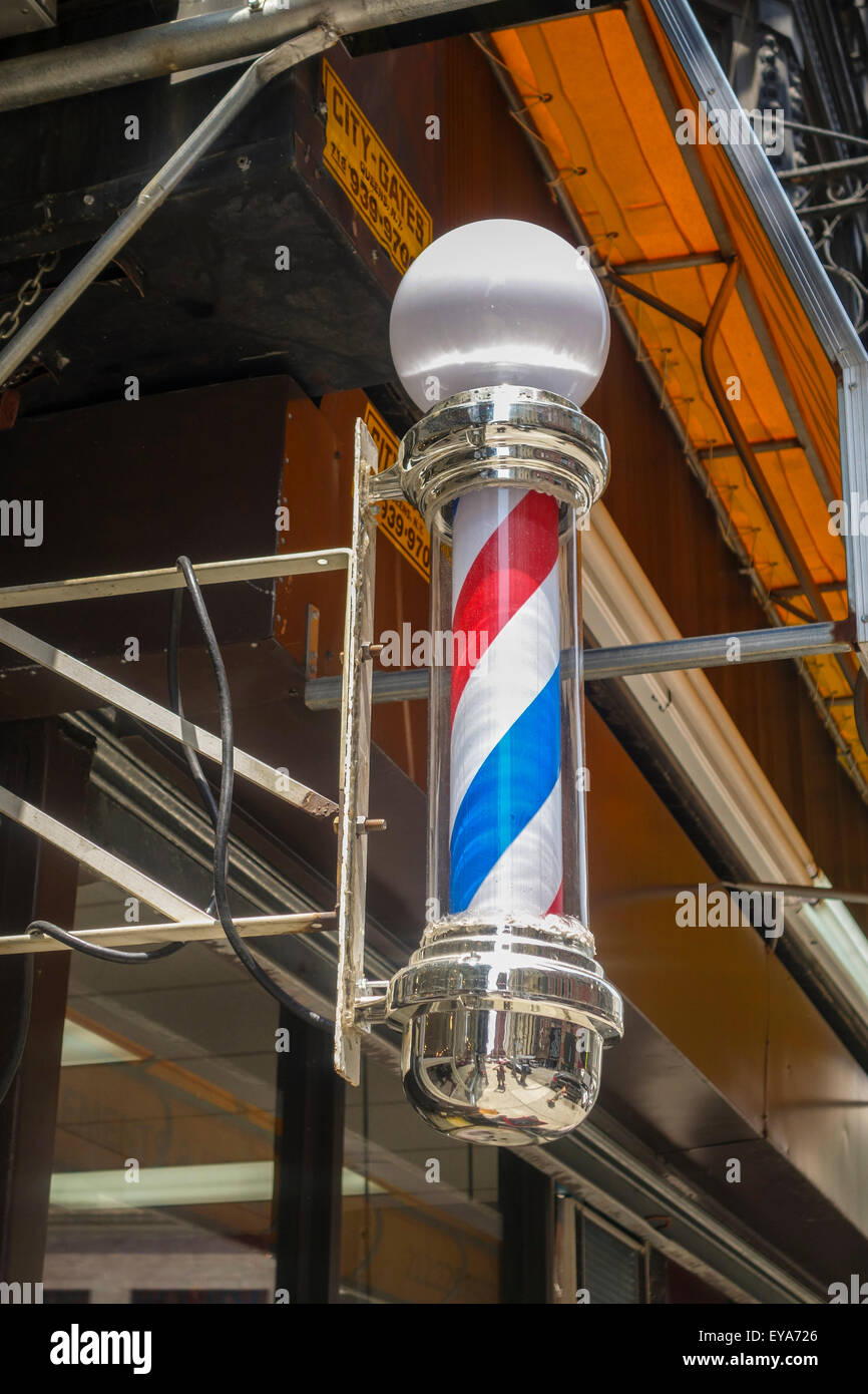 A classic American Barber's pole in front of Barber shop, New york city, Manhattan, USA. - Stock Image