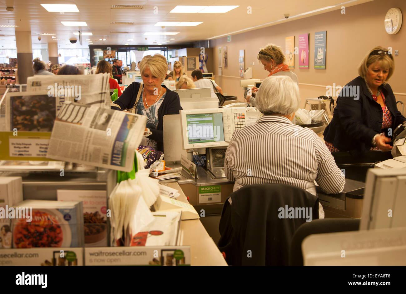 People at supermarket check-outs inside Waitrose store, Marlborough, Wiltshire, England, UK - Stock Image