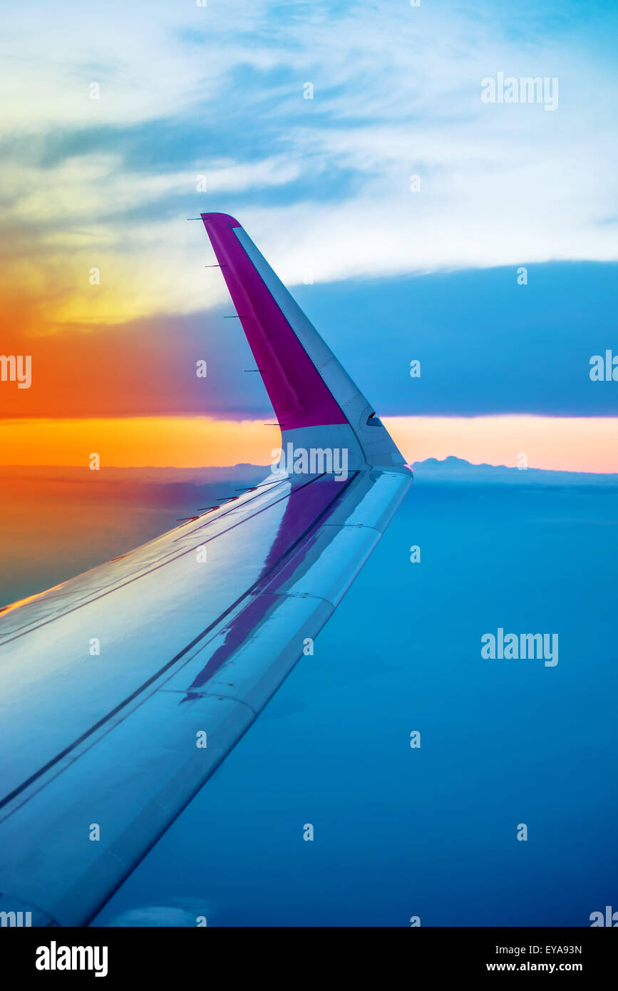 Airplane Wing Seen Through Open Porthole Window During the Flight of Commercial Passenger Aircraft, Sunset on Horizon - Stock Image
