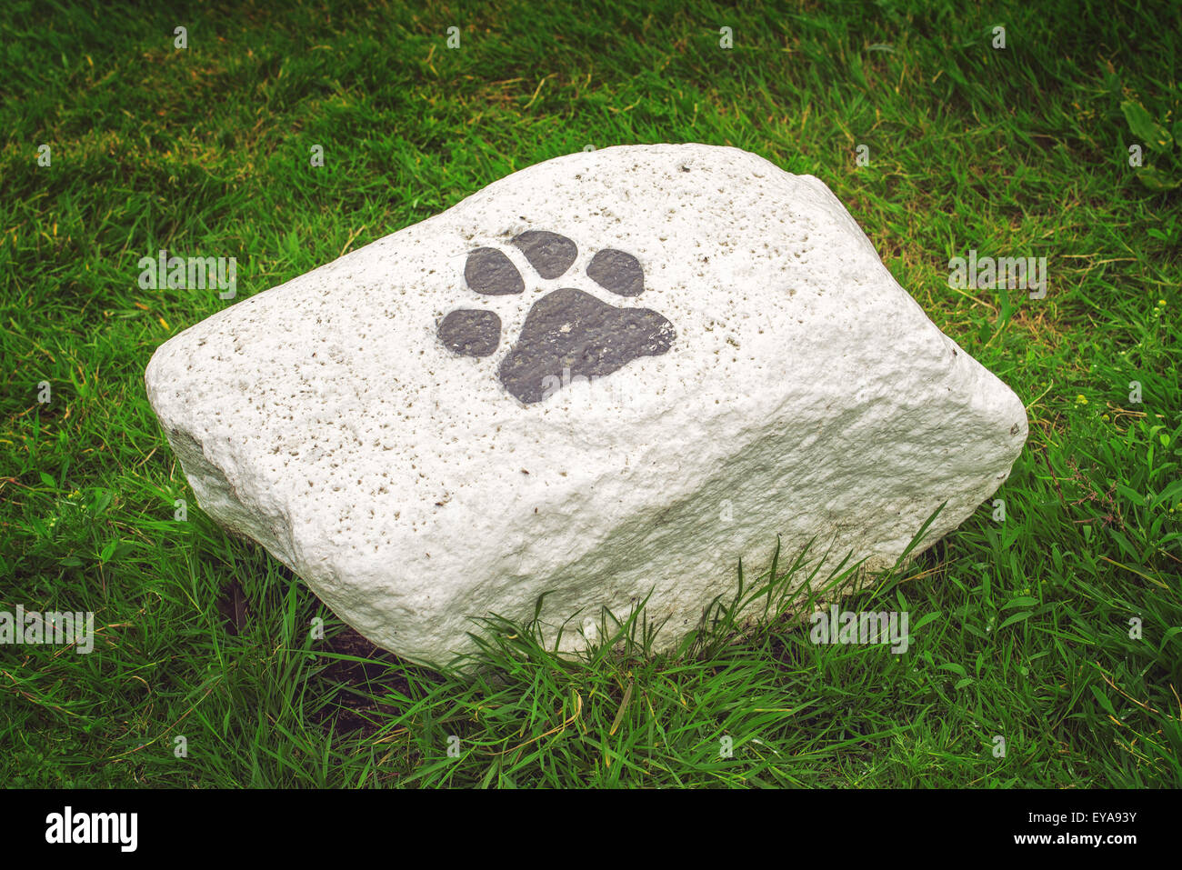 White Stone with Dog Paw Symbol as Pet Space Boundary Marking in Park - Stock Image
