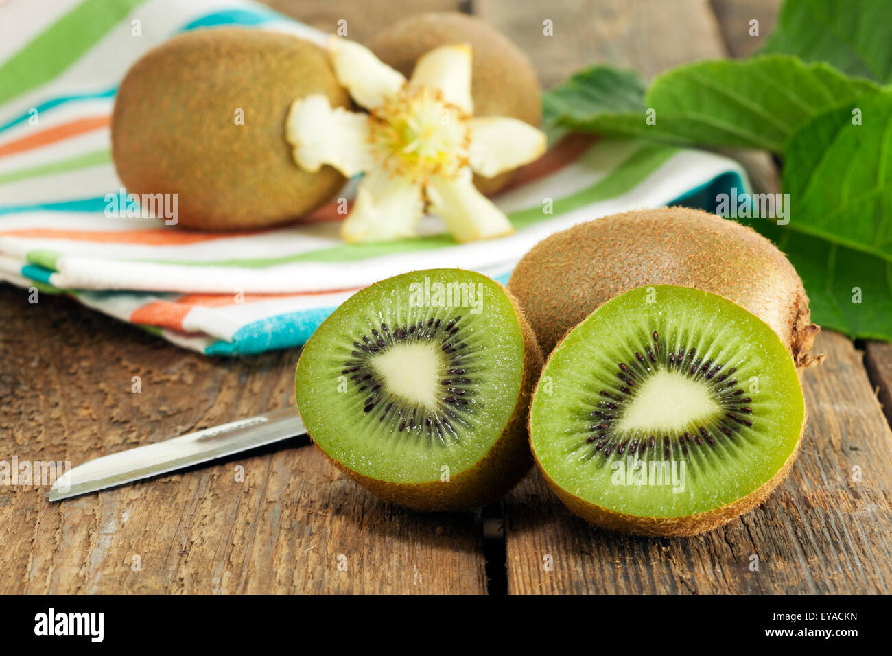 Whole and halved kiwi fruits with leaves and blossom on wooden table - Stock Image