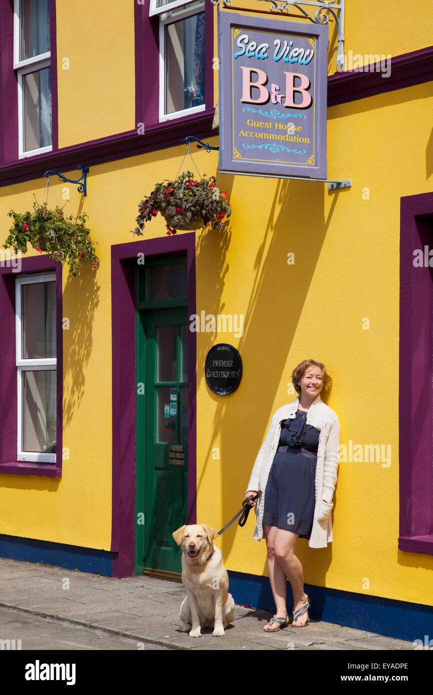 A Woman Leans Against A Colourfully Painted Building With Her Golden Retriever; Allihies, County Cork, Ireland - Stock Image