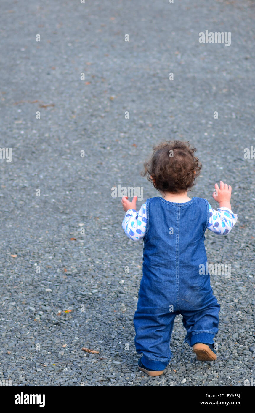 Little child (girl age 01) just starting to walk the first step. concept with copy space - Stock Image