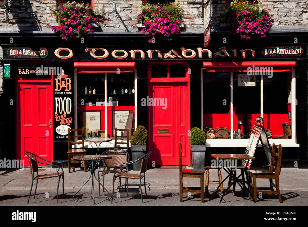 Seating outside a pub with red doors - Stock Image