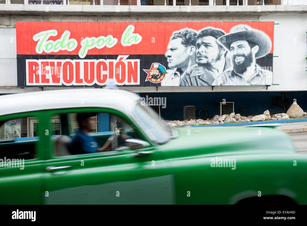 HAVANA, CUBA - JUNE 12, 2011: Vintage American car passes in front of billboard promoting Communist propaganda on - Stock Image
