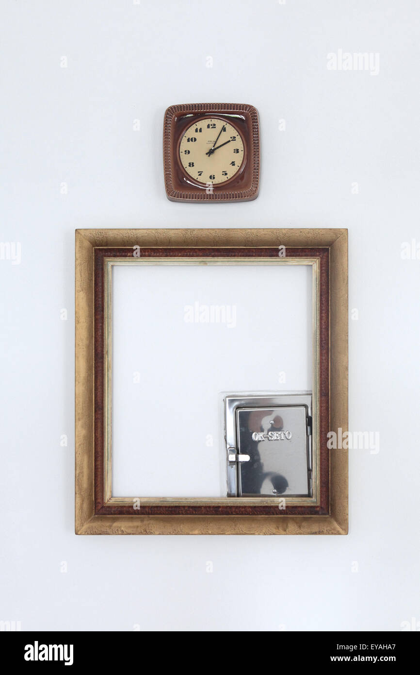 Clock and empty frame. Detail of a room decoration in the hotel Pension na Statku in the village of Bavorovice near - Stock Image
