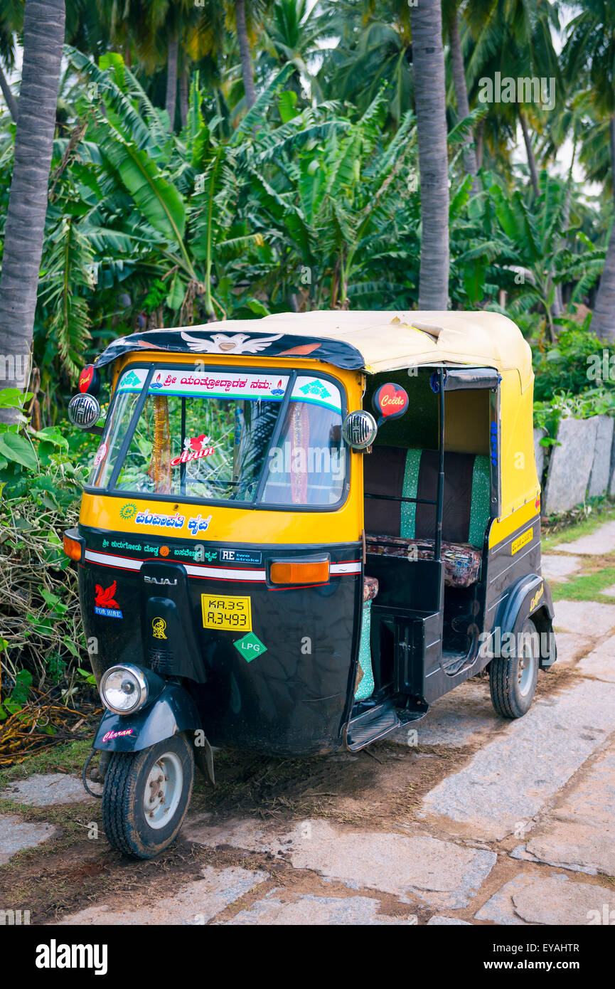 HAMPI, INDA - OCTOBER 31, 2012: Colorful moto rickshaw sits parked waiting for passengers on an empty path. - Stock Image