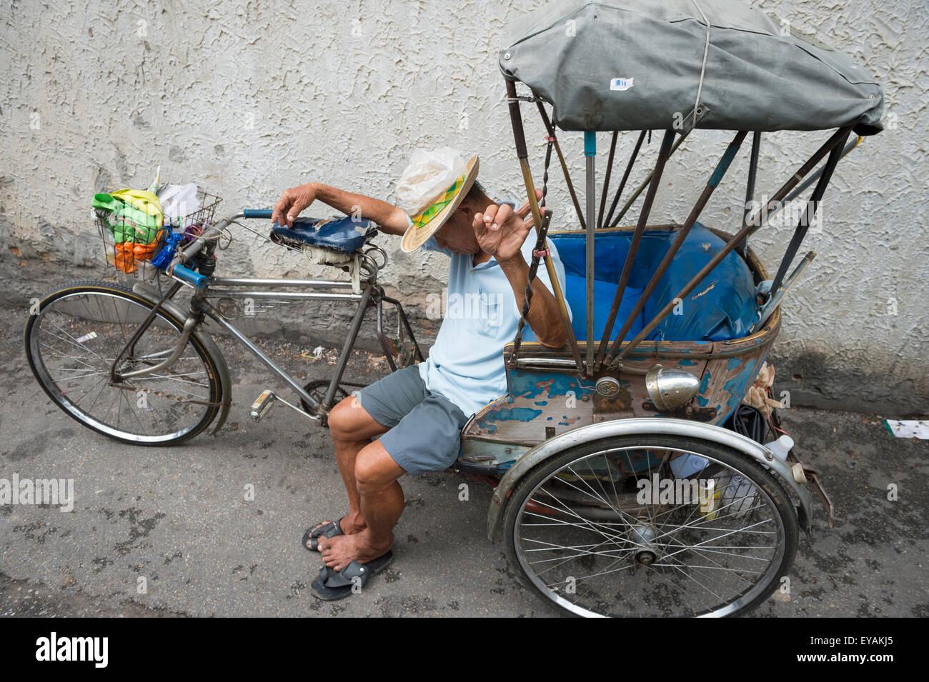 CHIANG MAI, THAILAND - NOVEMBER 07, 2014: Driver of a traditional bicycle rickshaw takes a nap on a quiet side street. - Stock Image