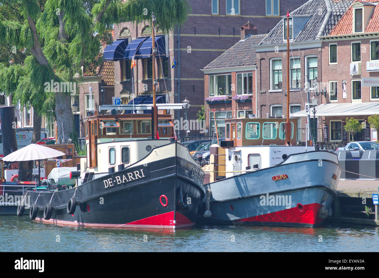 two old retro tugs tied up on the town quay Enkhuizen Holland.  A town on the Ijsselmeer . - Stock Image
