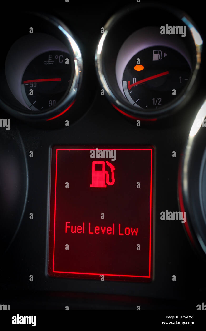 Low fuel warning light displayed on a car dashboard - Stock Image