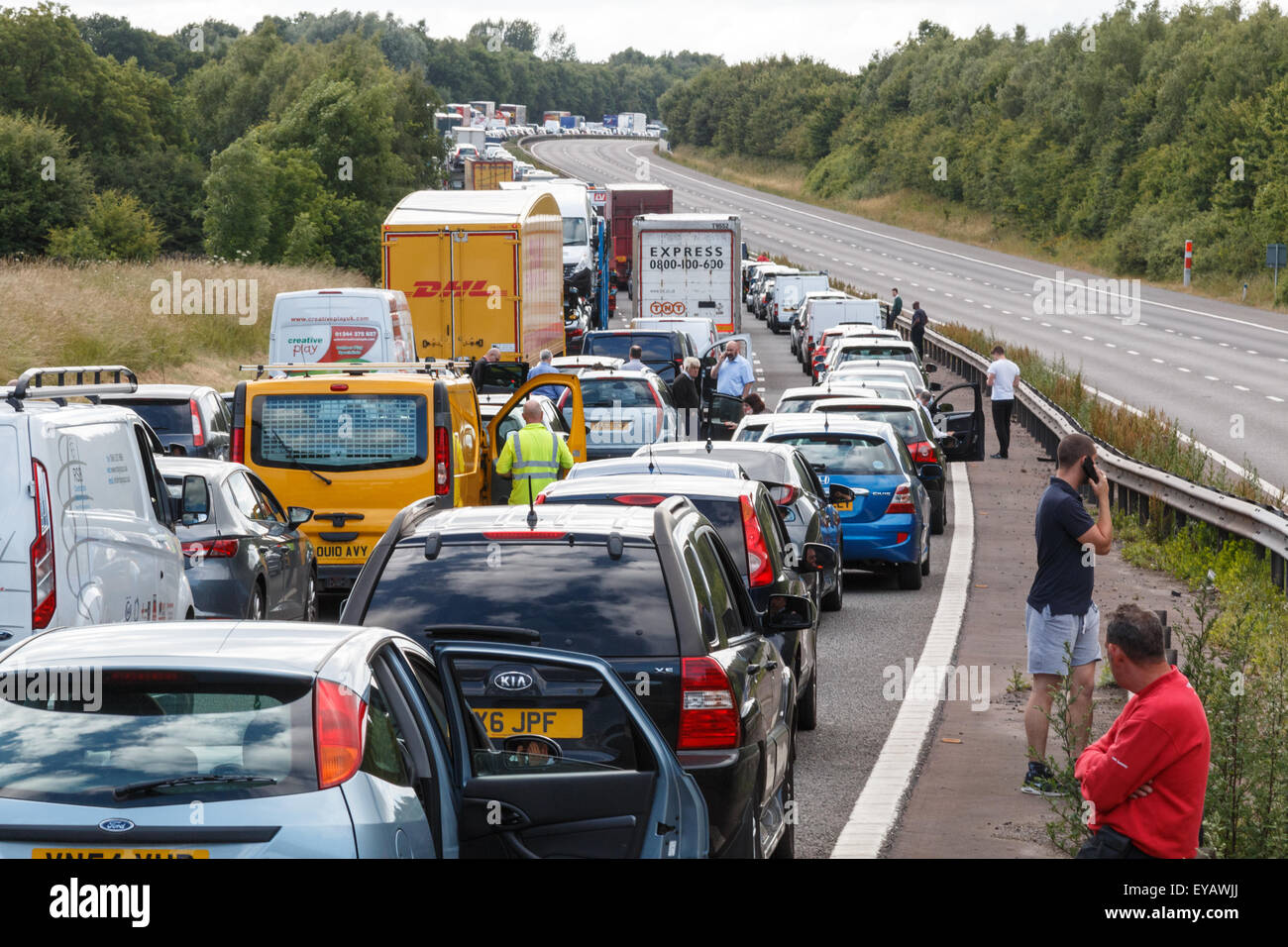 Traffic Jam with stationary traffic on a motorway in the UK  with people walking on the road - Stock Image