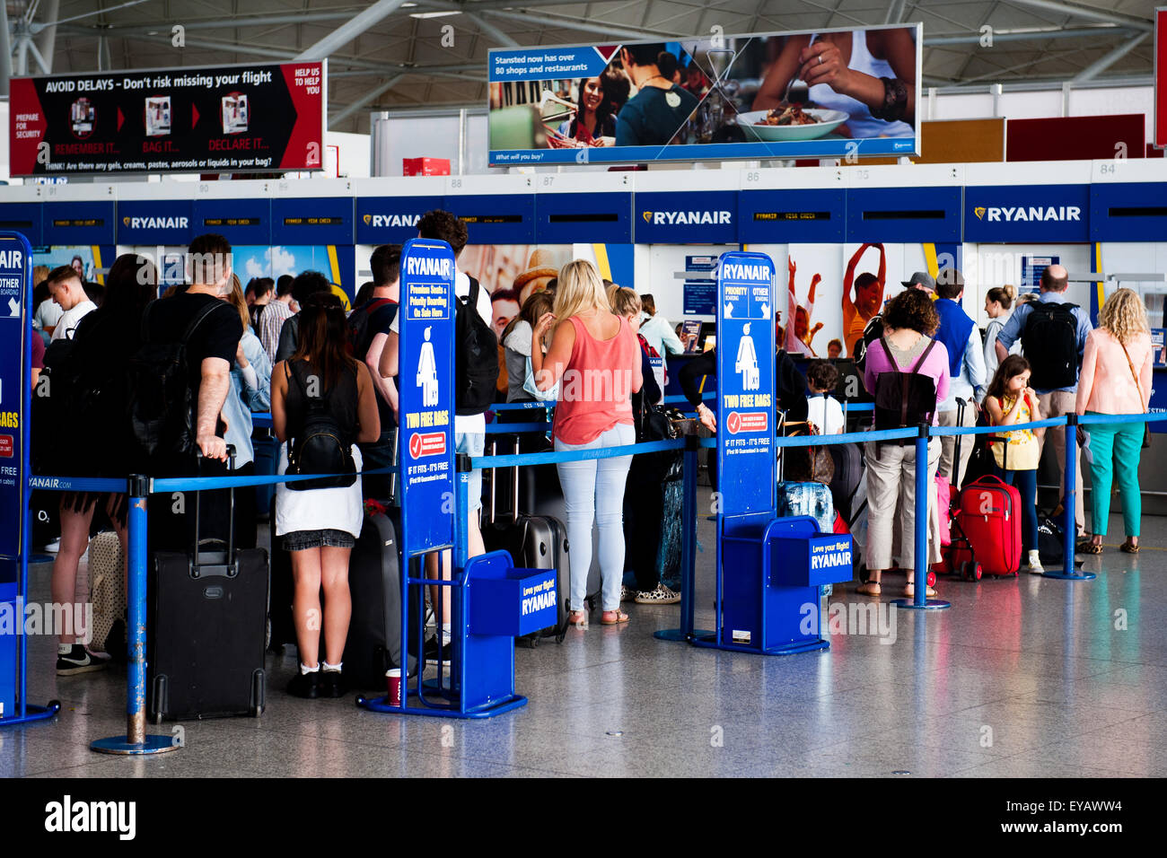 Passengers queue to drop luggage at busy Ryan Air check in desk in Stansted Airport, UK - Stock Image