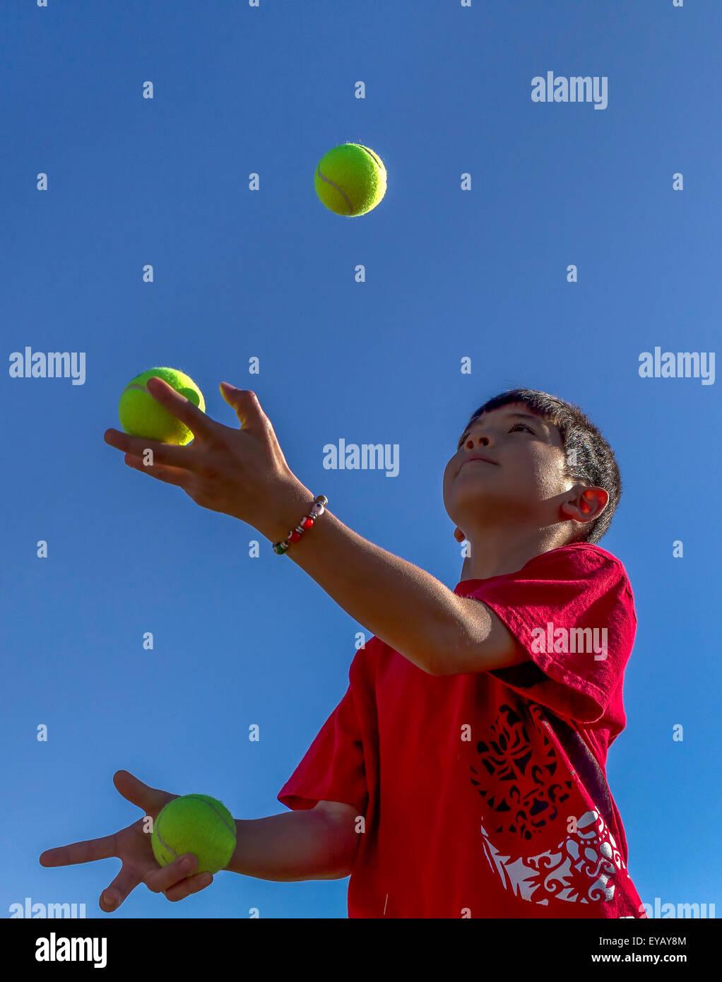 Boy tries juggling. - Stock Image