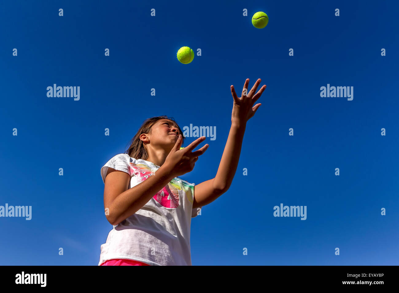 Looking up at girl juggling. - Stock Image