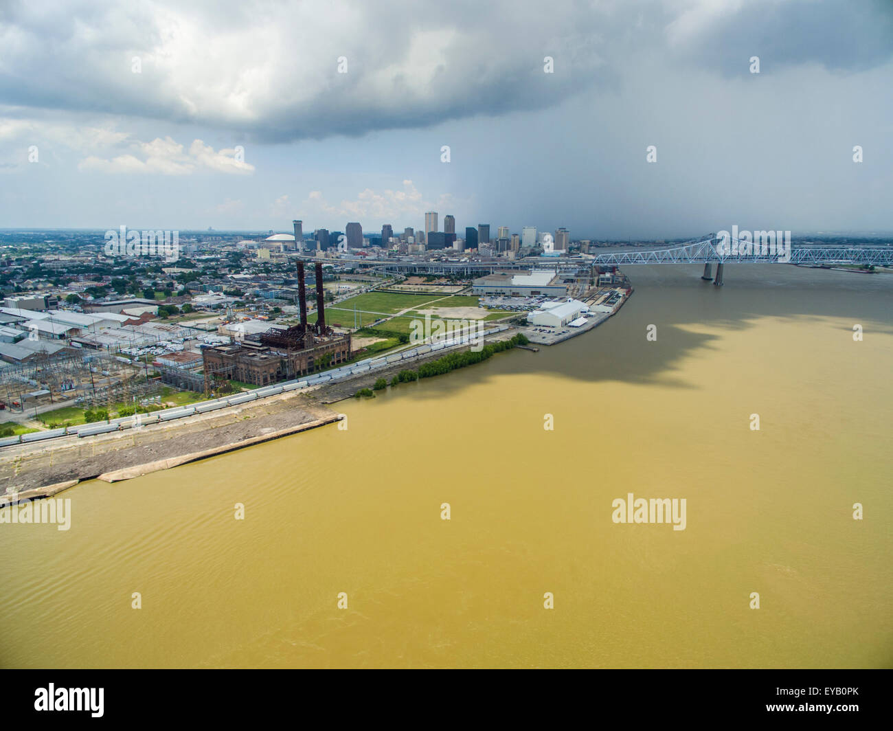 The dirty Mississippi River flowing through New Orleans with an ominous, dark cloud in the background. - Stock Image