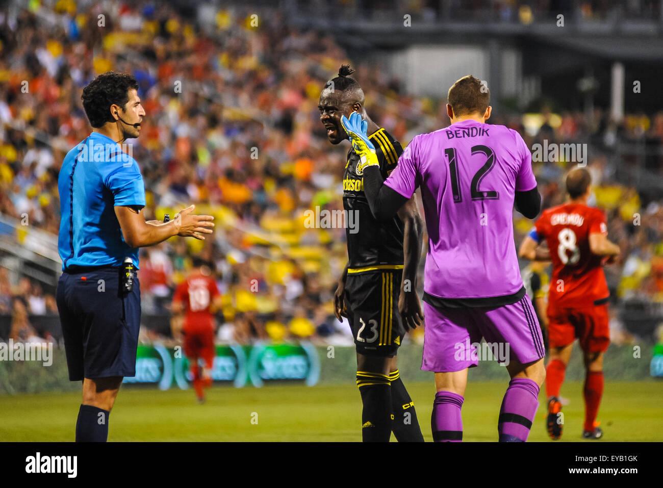 Columbus Crew SC forward Kei Kamara (23) disagreeing with the referee as Toronto FC goalkeeper Joe Bendik (12) walks Stock Photo