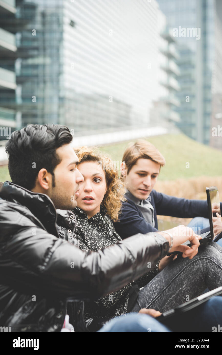 Multiracial contemporary business people seated on a bench working outdoor using notebook and tablet - finance,business, - Stock Image