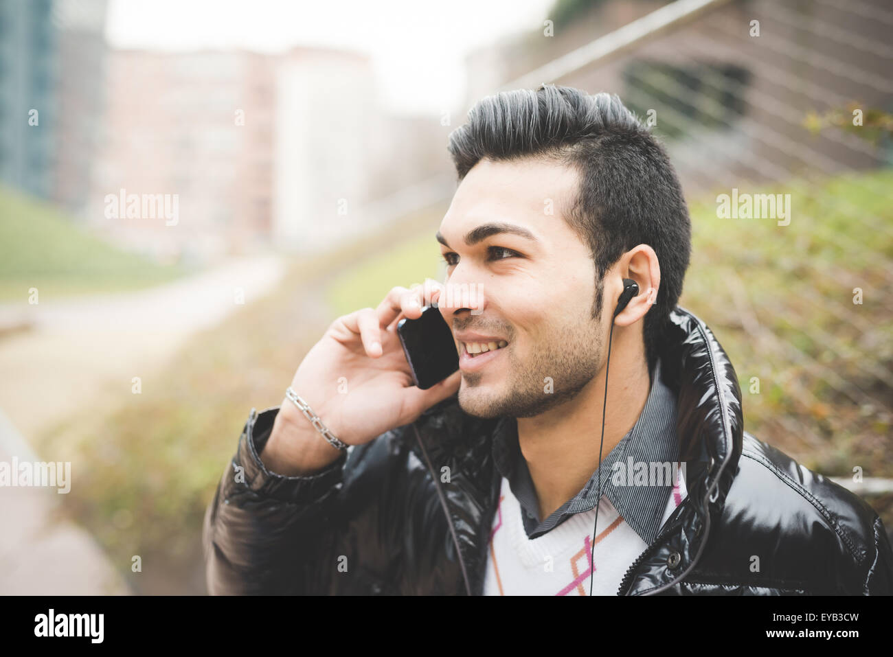 Headshot of a young handsome indian contemporary businessman talking smartphone with earphone already on - business, - Stock Image