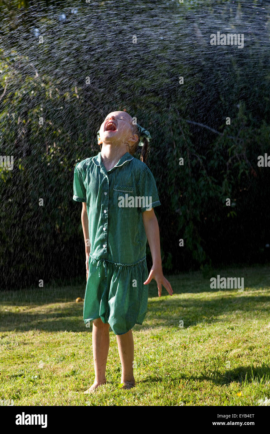 Girl in green dress playing under a water sprinkler. - Stock Image