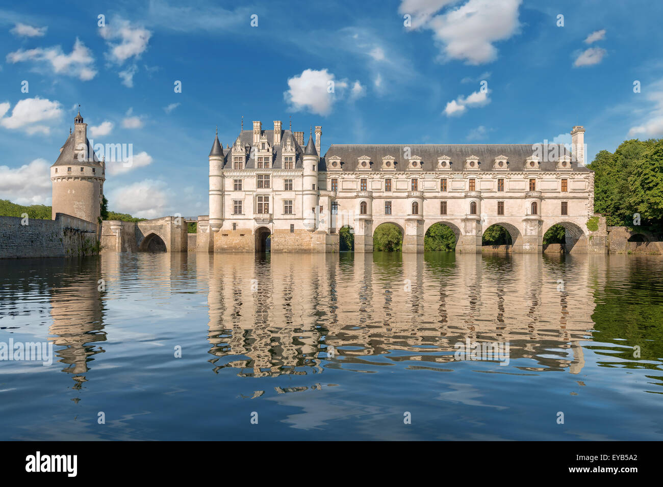 Chenonceau castle built over the cher river loire valleyfrance view from the river on gradient blue cloudy sky background
