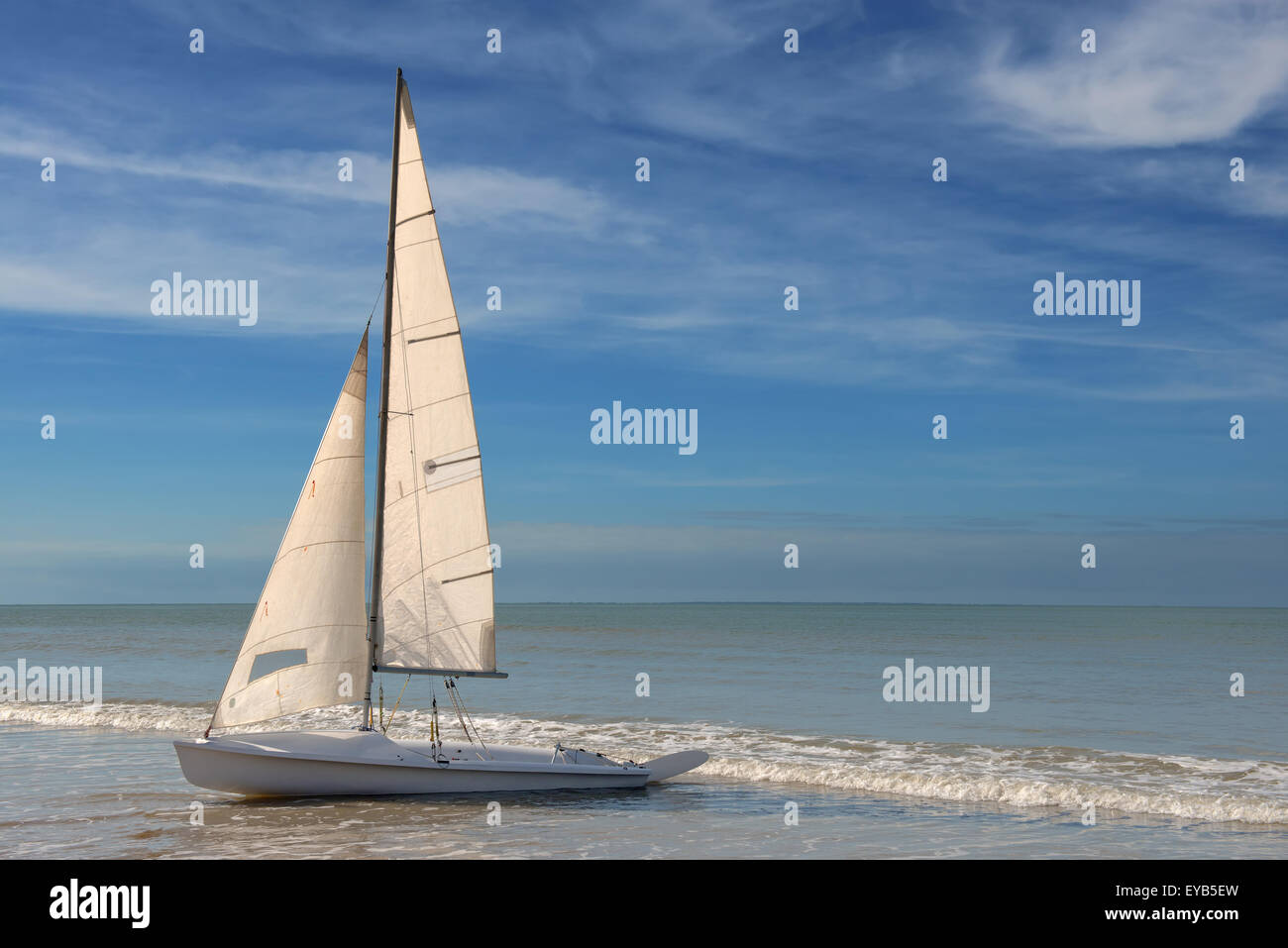 little white sailboat grounded on a beach on blue cloudy background - Stock Image
