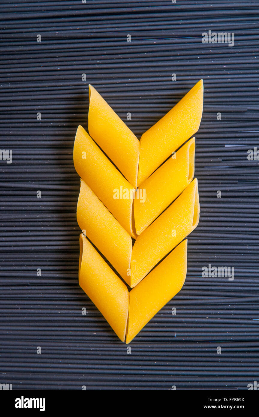 Pasta composition. Ear made of macaroni on black spaghetti background. - Stock Image