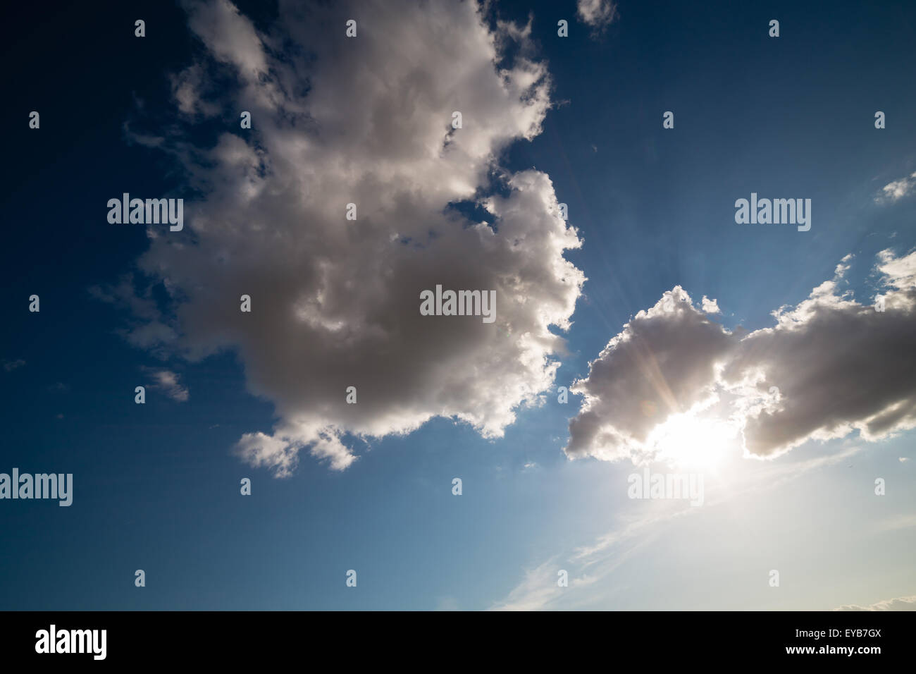 Sun going down behind fluffy clouds - Stock Image